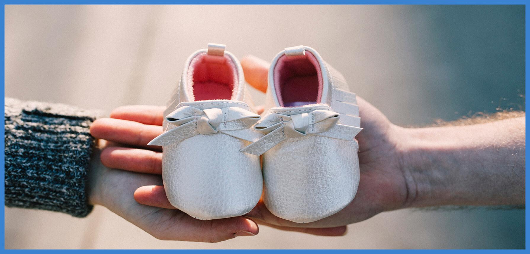 patucos de bebe en manos de sus papas